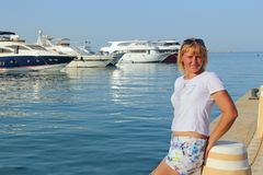 Mulher atrativa que relaxa na frente marítima Menina bonita que descansa perto do porto imagem de stock