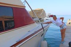 Mulher atrativa que relaxa na frente marítima Menina bonita que descansa perto do porto imagem de stock royalty free