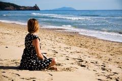 Mulher atrativa que senta-se em uma costa de mar Foto de Stock Royalty Free
