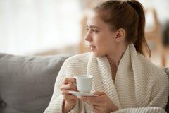 Mulher atrativa que senta-se na xícara de café da posse do sofá fotografia de stock royalty free