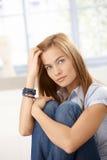 Mulher atrativa que senta-se no assoalho que abraça joelhos foto de stock