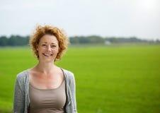 Mulher atrativa que sorri fora pelo campo verde Fotografia de Stock Royalty Free