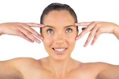 Mulher atrativa que toca em sua cara e que olha para cima Imagens de Stock Royalty Free