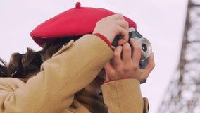 Mulher atrativa que toma fotos com a câmera, procurando um bom tiro, passatempo filme