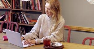 Mulher atrativa que usa o portátil na biblioteca filme