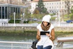 Mulher atrativa que usa o tablet pc na rua. fotografia de stock