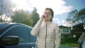 Mulher atrativa que usa o telefone celular durante a caminhada em ruas filme