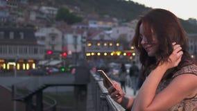 Mulher atrativa que usa o telefone celular em ruas da cidade da noite Movimento lento video estoque