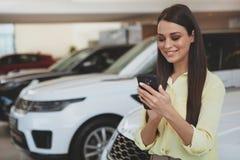 Mulher atrativa que usa seu telefone esperto ao bying o carro novo imagem de stock