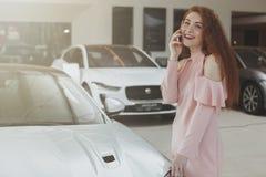 Mulher atrativa que usa seu telefone esperto ao bying o carro novo fotografia de stock royalty free