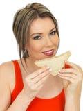 Mulher atrativa saudável nova que come um sanduíche do pão de mistura dos salmões e do pepino Foto de Stock