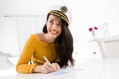 A mulher atrativa sorri assento e a tabela branca e a escrita com pena fotos de stock
