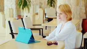 A mulher atrativa tem um bate-papo video sobre a tabuleta O vídeo chama o conceito das férias vídeos de arquivo