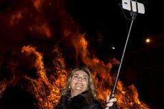 A mulher atrativa toma um selfie na frente de um fogo grande Imagens de Stock