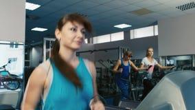 A mulher atrativa treinou no gym, correndo em uma escada rolante vídeos de arquivo