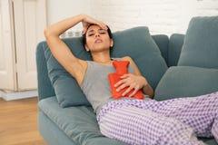 Mulher atrativa triste nova que tem a dor de estômago dolorosa da dor do período e dos grampos menstruais imagens de stock