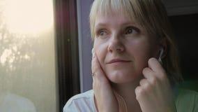 A mulher atrativa viaja pelo trem, escuta a música em fones de ouvido video estoque