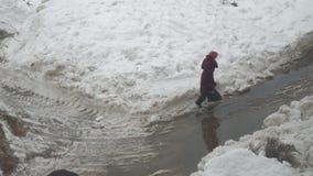 A mulher atravessa uma poça e uma neve molhada video estoque