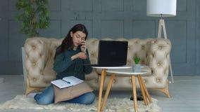 Mulher autônomo nova ocupada que trabalha no escritório domiciliário vídeos de arquivo