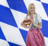 Mulher bávara de sorriso com coração de Oktoberfest fotografia de stock royalty free