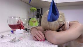 Mulher bêbada que dorme na tabela perto do vidro do álcool video estoque