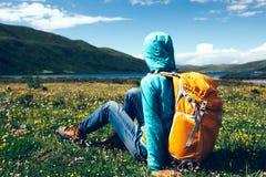 A mulher Backpacking senta-se em flores e em grama em montanhas da alta altitude imagem de stock royalty free