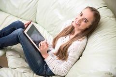 Mulher bautiful nova que usa o PC da tabuleta em casa Imagem de Stock