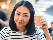 A mulher bebe o café no copo quente foto de stock royalty free