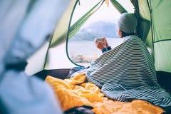 A mulher bebe o chá quente na barraca de acampamento e aprecia-o com eveni do outono fotos de stock