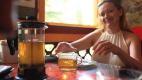 A mulher bebe o chá verde de um bule transparente Os amigos comem o alimento chinês em um restaurante chinês vídeos de arquivo