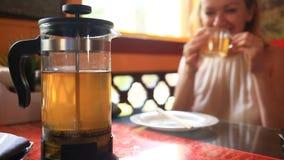 A mulher bebe o chá verde de um bule transparente Os amigos comem o alimento chinês em um restaurante chinês video estoque
