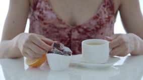 A mulher bebe um chá e doce de fruta comer na tabela branca video estoque