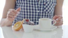 A mulher bebe um chá e doce de fruta comer na tabela branca vídeos de arquivo