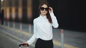 Mulher bem sucedida à moda com o táxi de espera da mala de viagem video estoque