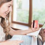 Mulher bem sucedida bonita que guarda o cartão de crédito, e comprando através do portátil Fotografia de Stock