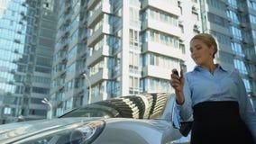 A mulher bem sucedida compra auto luxuoso, gerencie no alarme do carro, assentimento da aprovação, riqueza video estoque