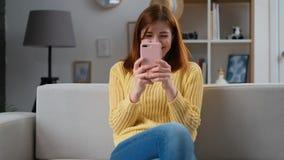 Mulher bem sucedida nova que usa a casa da sala de visitas do app do smartphone em casa A menina excitada que recebe a boa notíci filme