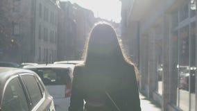 Mulher bem sucedida que anda lentamente abaixo da rua, feixes brilhantes do sol que iluminam a video estoque