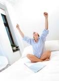 Mulher bem sucedida que trabalha na cama imagens de stock