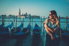 Mulher bem vestido bonita que está perto do quadrado de San Marco com gôndola e da ilha de Santa Lucia no fundo Imagens de Stock