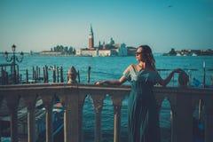 Mulher bem vestido bonita que está perto do quadrado de San Marco com gôndola e da ilha de Santa Lucia no fundo Foto de Stock