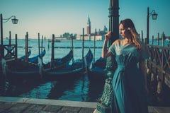 Mulher bem vestido bonita que está perto do quadrado de San Marco com gôndola e da ilha de Santa Lucia no fundo Imagem de Stock Royalty Free