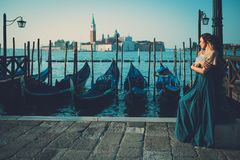 Mulher bem vestido bonita que está perto do quadrado de San Marco com gôndola e da ilha de Santa Lucia no fundo Fotos de Stock Royalty Free