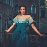 Mulher bem vestido bonita que levanta em uma ponte sobre o canal em Veneza imagens de stock royalty free