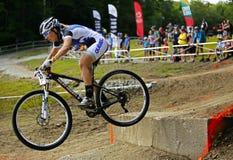 A mulher biking da montanha dos jogos de Canadá salta o ar Fotografia de Stock