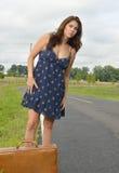 Mulher biracial bonita que senta-se na mala de viagem pela estrada Imagens de Stock