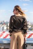 Mulher bonita à moda do retrato da forma da rua com óculos de sol e saco que levanta na cidade, seu cabelo que vibra no vento Imagens de Stock
