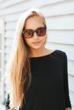 Mulher bonita à moda nos óculos de sol perto de uma parede de madeira imagem de stock royalty free