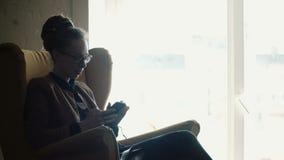 Mulher bonita à moda nos vidros que passa o tempo no Internet, usando o smartphone em compartilhar o espaço vídeos de arquivo