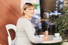 A mulher bonita é de sorriso e de vista na câmera Fotografia de Stock Royalty Free